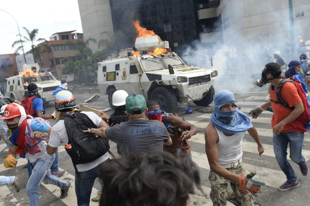 A charging National Guard riot control vehicle is hit by a Molotov cocktail thrown by a demonstrator during a protest against Venezuelan President Nicolas Maduro, in Caracas on May 3, 2017. (Photo by Federico Parra/AFP Photo)