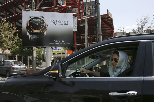 A woman drives in front of an advertising billboard for Bulgari watches in northern Tehran, Iran, Saturday, July 18, 2015. While it will likely be months before sanctions on Iran ease, business and political leaders are wasting no time in trying to tap into a large and what they hope will be a lucrative Iranian market. Ads for European cars and luxury goods are starting to reappear in Tehran. American firms, though, have to be much more cautious. Deal or no deal, U.S. sanctions not related to the nuclear program will still be in place and bar most American companies from doing business with Iran. (Photo by Vahid Salemi/AP Photo)