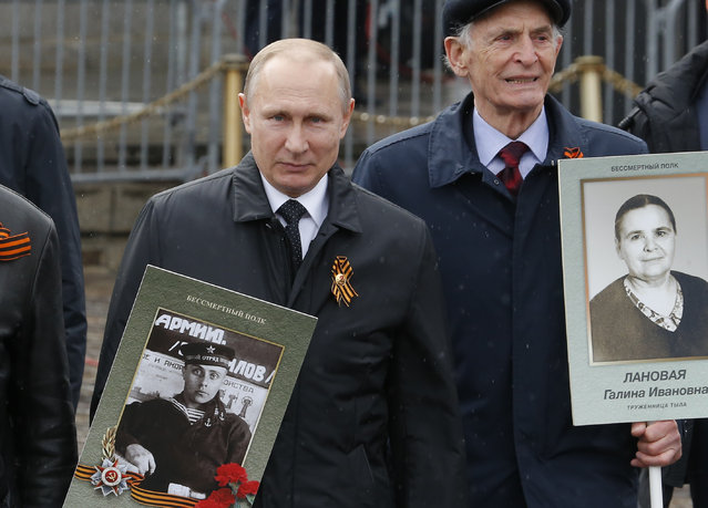 Russian President Vladimir Putin holds the portrait of his father, war veteran Vladimir Spiridonovich Putin, as he attends the Immortal Regiment march during the 72nd anniversary of the end of World War II on the Red Square in Moscow, Russia on May 9, 2017. (Photo by Sergei Karpukhin/Reuters)