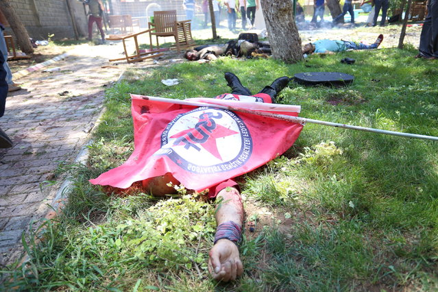 A victim, with a flag of the left-wing Federation of Socialist Youth Associations covering him, lies on the ground following an explosion in Suruc, in the southeastern Sanliurfa province, Turkey, July 20, 2015. The explosion outside a cultural centre in the Turkish town of Suruc near the border with Syria killed at least 20 people and wounded many more on Monday, witnesses told Reuters, in what local officials said may have been a suicide bombing. (Photo by Ozcan Soysal/Reuters/Depo)