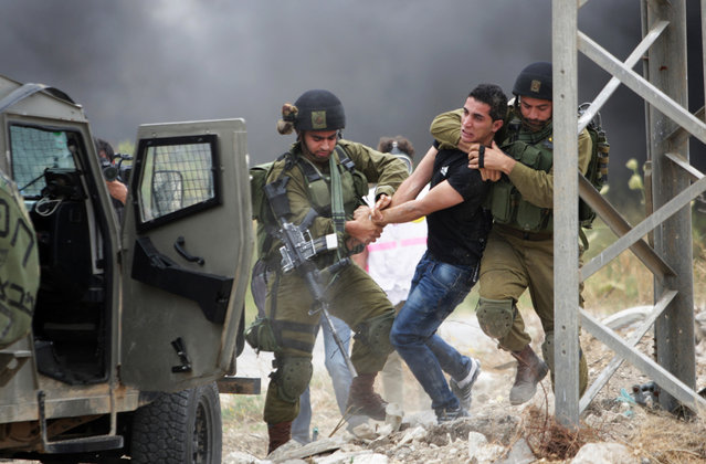 Israeli soldiers detain a protester during a demonstration by Palestinians protesting against the Israeli-built West Bank separation barrier and calling for the right of return for Palestinian refugees, in the northern West Bank city of Tulkarem, on May 31, 2014. (AP Photo/Nasser Ishtayeh)