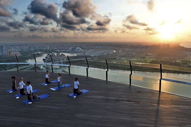 World number three tennis player Simona Halep of Romania (2nd L) takes part in a yoga session at skypark observation deck at the top of the Marina Bay Sands in Singapore on July 22, 2015. Halep made a one-day appearance in Singapore as the countdown to the BNP Paribas WTA finals in October. (Photo by Roslan Rahman/AFP Photo)