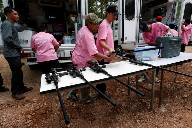 Officials prepare weapons with a sedation as they start moving tigers from Thailand's controversial Tiger Temple, a popular tourist destination which has come under fire in recent years over the welfare of its big cats in Kanchanaburi province, west of Bangkok, Thailand, May 30, 2016. Wildlife authorities raid a Buddhist temple that has more than 100 tigers, taking away three cats and vowing to confiscate scores more in response to global pressure over wildlife trafficking. (Photo by Chaiwat Subprasom/Reuters)