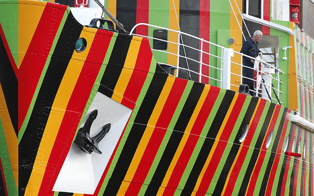 """A man stands on the deck of the brightly painted former pilot ship The Edmund Gardner at the Albert Dock in Liverpool, northern England, June 11, 2014. The ship has been newly painted by artist Carlos Cruz-Diez using the idea of """"Dazzle"""" camouflage which was a system of camouflaging used by allied shipping in the First World War in an attempt to confuse german submarines and is part of the Liverpool Biennial art festival. (Photo by Phil Noble/Reuters)"""