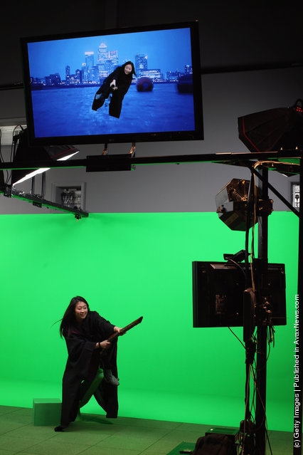 A girl rides a broomstick in front of a green screen at the new Harry Potter Studio Tour at Warner Brothers Leavesden Studios