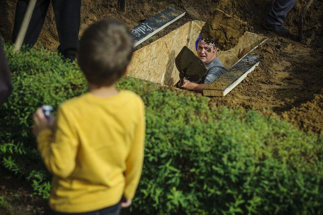 A gravedigger competes as a boy looks on during the first National Grave Digging competition at the public cemetery of Debrecen, 226 km east of Budapest, Hungary, Friday, June 3, 2016. (Photo by Zsolt Czegledi/MTI via AP Photo)