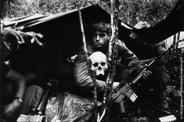 A human skull keeps watch over US soldiers encamped in the Vietnamese jungle during the Vietnam War, 1968