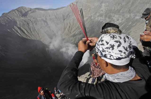 A worshipper prays at the crater of Mount Bromo during Yadnya Kasada festival in Probolinggo, East Java, Indonesia, Saturday, August 1, 2015. Every year people gather for the annual festival where offerings of rice, fruit, vegetables, livestock or money are made to Hindu gods at the active volcano to ask for blessings and assure a bountiful harvest. (Photo by AP Photo/Trisnadi)
