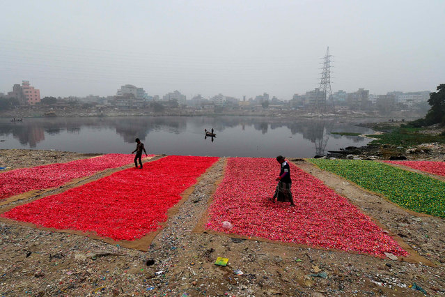 Workers spread out recycled plastic chips for them to dry on the banks of the Buriganga River in Dhaka on December 19, 2019. (Photo by Munir Uz Zaman/AFP Photo)