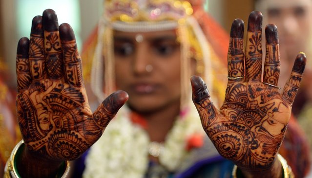 An Indian bride shows her mehendi (henna)-decorated hands as she waits her turn to be wedded at a multi-faith mass wedding in Mumbai on June 22, 2014. Over 50 underprivileged couples from different communities were wedded according to the traditions of their faith on the occassion. (Photo by Indranil Mukherjee/AFP Photo)