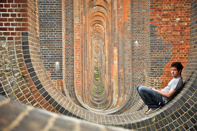 Mike poses against a curved wall which looks like an optical illusion. (Photo by Mike Deere/Caters News)