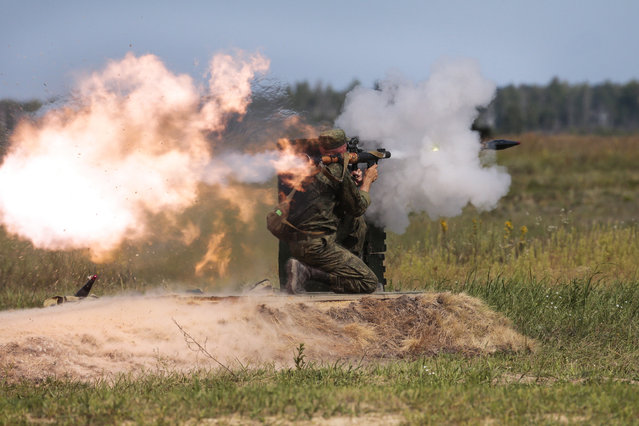 "A Russian paratrooper fires a weapon during the ""Paratrooper's platoon"" military game at a Dubrovichi shooting range outside of Ryazan, some 170 kms south east of Moscow, Russia, Tuesday, August 4, 2015. The competitions called the International Army Games involve troops from Russia and several other nations.  (Photo by Ivan Sekretarev/AP Photo)"