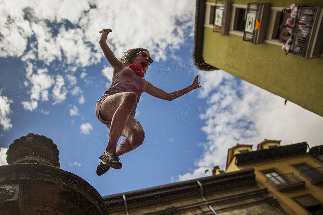 "A reveler jumps from a fountain onto the crowd below, after the launch of the ""Chupinazo"" rocket, to celebrate the official opening of the 2014 San Fermin fiestas in Pamplona, Spain, Sunday, July 6, 2014. Revelers from around the world turned out here to kick off the festival with a messy party in the Pamplona town square, one day before the first of eight days of the running of the bulls glorified by Ernest Hemingway's 1926 novel ""The Sun Also Rises"". (Photo by Andres Kudacki/AP Photo)"