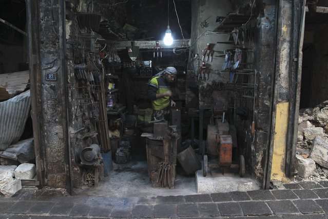 A blacksmith works at his shop in the old city of Aleppo January 6, 2015. (Photo by Jalal Al-Mamo/Reuters)