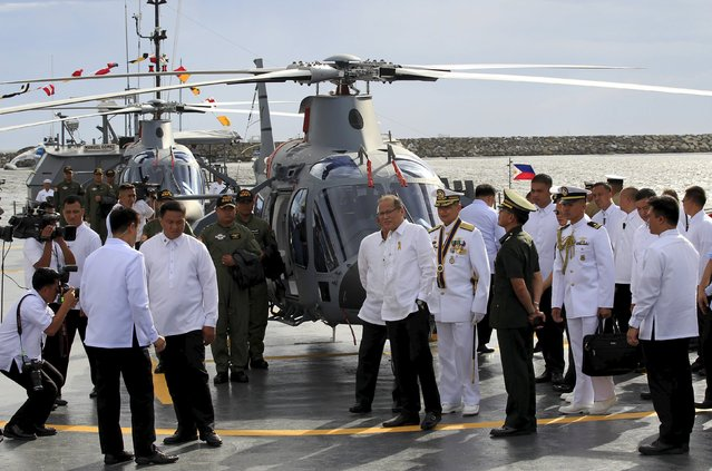 Philippine President Benigno Aquino (C) walks with Rear Admiral Caesar Taccad, new Flag-Officer-in-Command of the Philippine Navy, as they inspect one of the two newly-acquired AW109E multi-purpose helicopter during his visit at the navy headquarters in Manila August 10, 2015. (Photo by Romeo Ranoco/Reuters)
