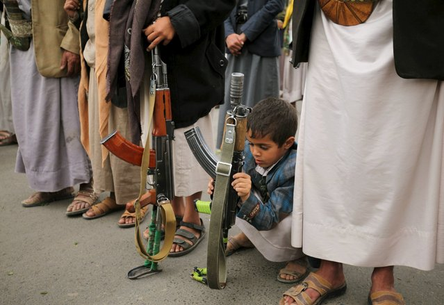 A boy holds his father's rifle during a rally by followers of the Houthi movement against the Saudi-led coalition in Yemen's capital Sanaa, August 11, 2015. Militiamen clashed with Yemen's dominant Houthi group inside the city of Ibb on Tuesday, residents said, in their latest significant advance into territory the Houthis had held unopposed for months. (Photo by Mohamed al-Sayaghi/Reuters)