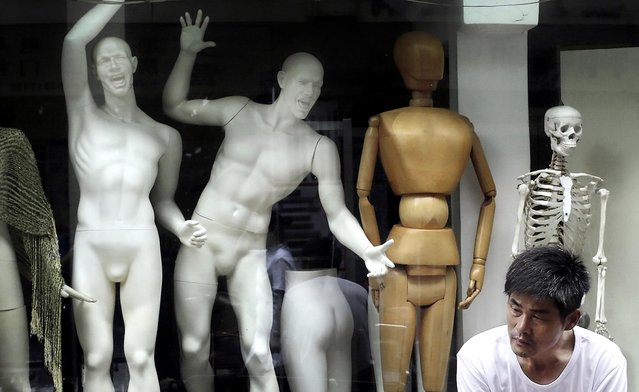 A man sits in front of mannequins on display at a shop in Shanghai, China on June 8, 2012