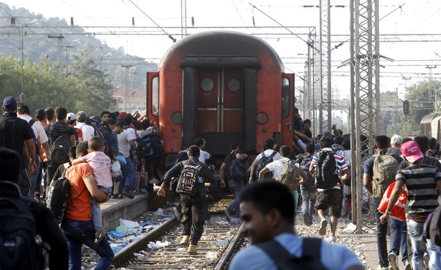 Migrants run to board a train that would take them towards Serbia, at the railway station in the southern Macedonian town of Gevgelija, on Wednesday, August 12, 2015. Macedonia is facing an increasing pressure of migrants flow on its southern and northern borders with Greece and Serbia as thousands of migrants from Middle East, Asia and Africa are heading north through the Balkans on their way to the more prosperous European Union countries. (Photo by Boris Grdanoski/AP Photo)