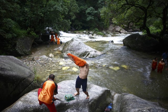 "A devotee removes his t-shirt before taking a dip in the Bagmati River during the ""Bol Bom"" (Say Shiva) pilgrimage in Kathmandu July 21, 2014. The faithful, chanting the name of Lord Shiva, run about 15 km (9 miles) barefooted toward Pashupatinath temple seeking good health, wealth and happiness. (Photo by Navesh Chitrakar/Reuters)"