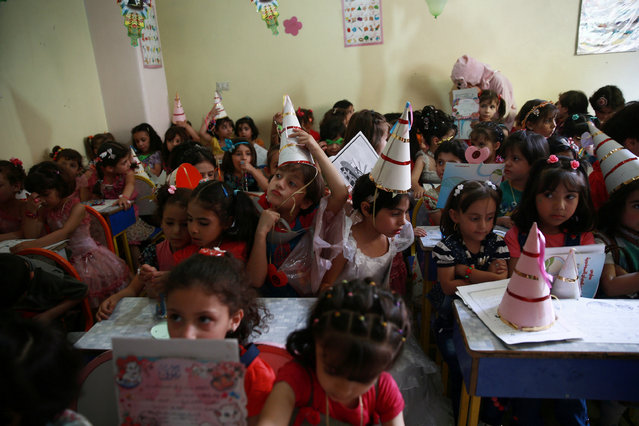 Girls attend a class celebration for successfully completing the school year, in the rebel-held besieged town of Douma, eastern Damascus suburb of Ghouta, Syria June 2, 2016. (Photo by Bassam Khabieh/Reuters)
