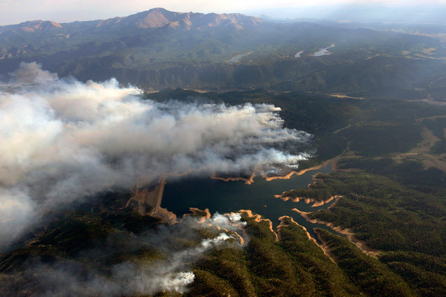 Smoke rises around Rampart Reservoir from the Waldo Canyon wildfire in this aerial photograph taken on June 27, 2012. (Reuters/John Wark)
