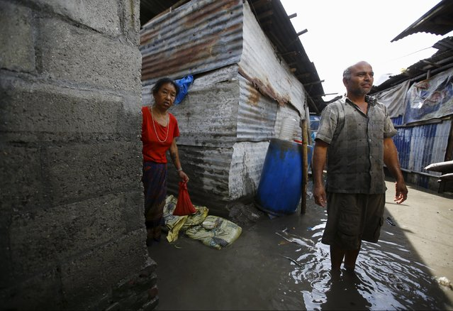 People living in a slum stand near their shed amid floodwaters caused by the heavy rainfall flowing from the swollen Bagmati River in Kathmandu, Nepal August 17, 2015. (Photo by Navesh Chitrakar/Reuters)