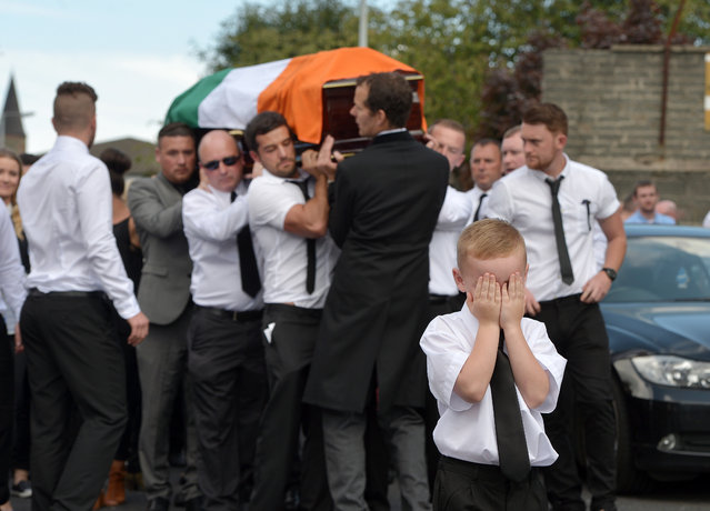 A young boy shows emotion as he covers his face while the funeral takes place of former IRA member Kevin McGuigan Sr on August 18, 2015 in Belfast, Northern Ireland. The father of nine was shot dead outside his home in the Short Strand area earlier this week after being told by police he was under threat from republicans. Mr. McGuigan was given the warning shortly after the killing of former IRA commander Gerard Davison in May of this year. (Photo by Charles McQuillan/Getty Images)