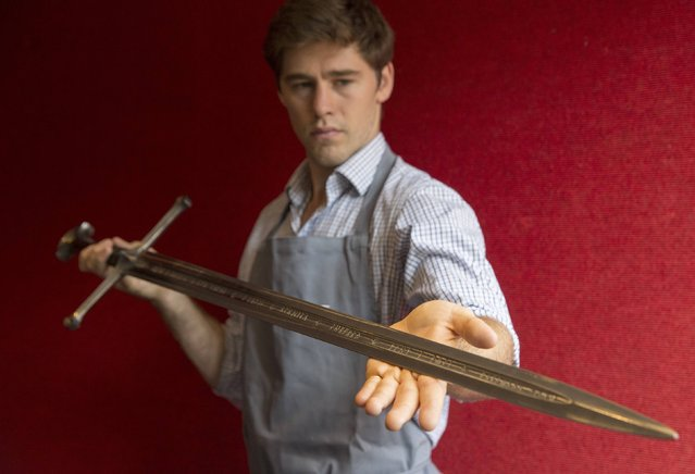 "A gallery assistant poses for a photograph with the sword ""Anduril"" which was used in the Lord of the Rings film ""Return of the King"" in Bonhams auction house in London July 31, 2014. The sword is part of a number  of props from the film that will be auctioned in New York on November 24. (Photo by Neil Hall/Reuters)"