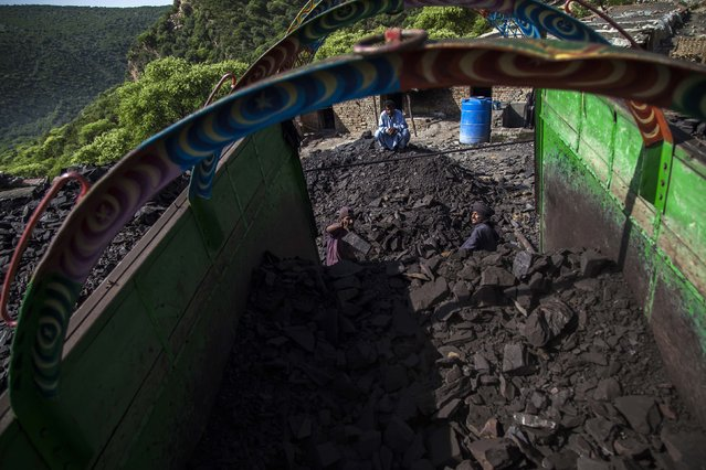 A miner loads coal onto a truck outside a mine in Choa Saidan Shah, Punjab province, April 29, 2014. (Photo by Sara Farid/Reuters)