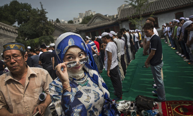 A Chinese Hui Muslim woman arrives for Eid al-Fitr prayers marking the end of the holy fasting month of Ramadan at the historic Niujie Mosque on July 6, 2016 in Beijing, China. Islam in China dates back to the 10th century as the legacy of Arab traders who ventured from the Middle East along the ancient Silk Road. Of an estimated 23 million Muslims in China, roughly half are Hui, who are ethnically Chinese and speak Mandarin. Photo by Kevin Frayer/Getty Images)