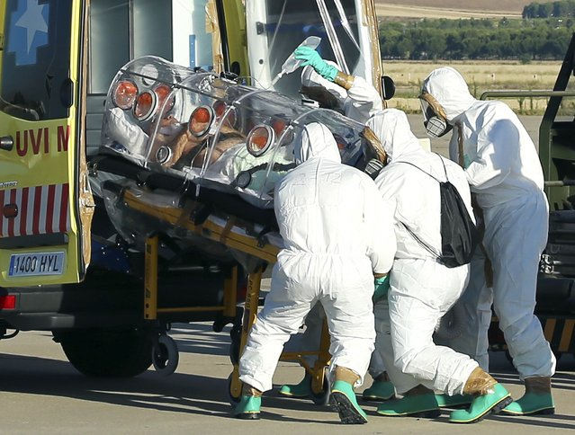 Health workers load Ebola patient, Spanish priest Miguel Pajares, into an ambulance on the tarmac of Torrejon airbase in Madrid, after he was repatriated from Liberia for treatment in Spain, August 7, 2014. Pajares, the first European infected by a strain of Ebola that has killed more than 932 people in West Africa, was stable in a Madrid hospital on Thursday after being airlifted from Liberia, health authorities said. (Photo by Reuters/Ministry of Defence)