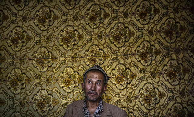 A Uyghur man waits to have his hair cut at a barber shop before the Eid holiday  on July 28, 2014 in old Kashgar, Xinjiang Province, China. (Photo by Kevin Frayer/Getty Images)