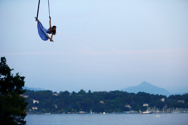 Russian acrobat Ekaterina Stepanova, currently on show with Swiss National Circus Knie in Geneva, performs under a hot air balloon next to Lake Leman in Geneva, Switzerland August 28, 2017. (Photo by Pierre Albouy/Reuters)