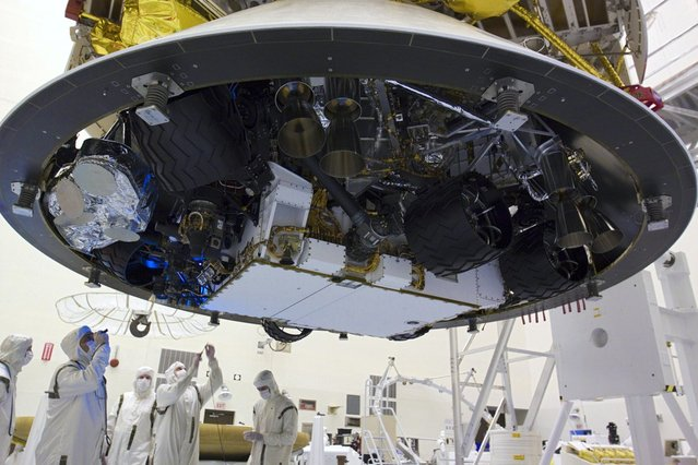 In the Payload Hazardous Servicing Facility at NASA's Kennedy Space Center in Florida, technicians inspect beneath NASA's Mars Science Laboratory (MSL) mission aeroshell, (containing the rover Curiosity), which has been mated to the cruise stage. (Photo by Glenn Benson/NASA)