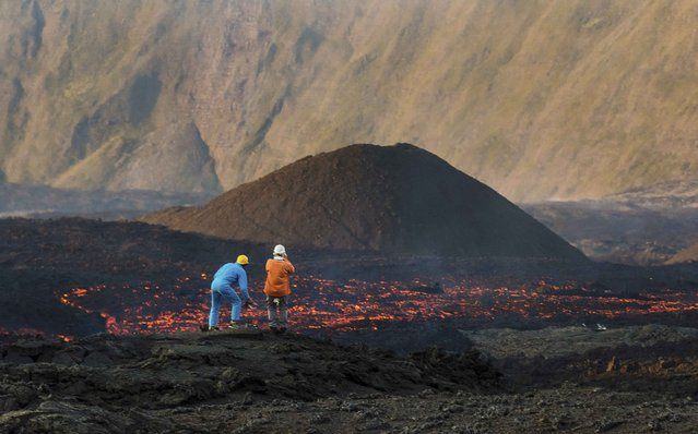 Two volcanologists stand on cooled volcanic rock as molten lava flows from the Piton de la Fournaise, one of the world's most active volcanoes, on the French Indian Ocean Reunion Island August 25, 2015. (Photo by Gilles Adt/Reuters)