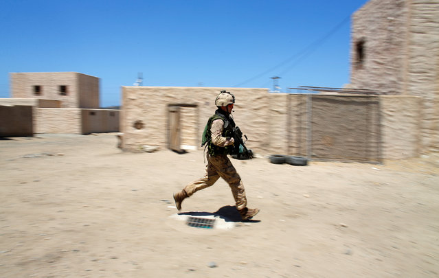 A Canadian soldier from the Royal 22nd Regiment runs through a simulated village as he trains during a non-combative extraction operation in urban terrain as part of Rim of the Pacific (RIMPAC) 2016 exercise held at Camp Pendleton, California United States, July 11, 2016. (Photo by Mike Blake/Reuters)