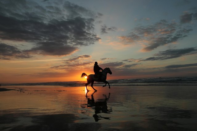 A Palestinian man rides a horse on a beach during the last sunset of 2019, in Gaza City on December 31, 2019. (Photo by Suhaib Salem/Reuters)