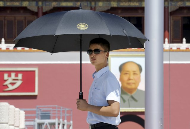 A paramilitary police officer in plain-clothes holding an umbrella keeps watch on Beijing's Tiananmen Square, August 27, 2015. Major Western leaders will not attend a military parade in China next week to mark the end of World War Two, leaving President Xi Jinping to stand with leaders and officials from Russia, Sudan, Venezuela and North Korea at his highest-profile event of 2015. (Photo by Jason Lee/Reuters)