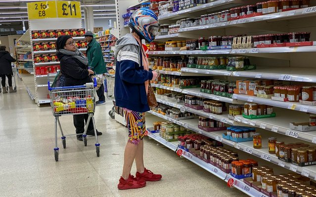 A woman wears a crash helmet whilst self distancing as she shops for groceries in a stocked up East London Tesco store, England on March 24, 2020. (Photo by Jeff Moore/The Telegraph)