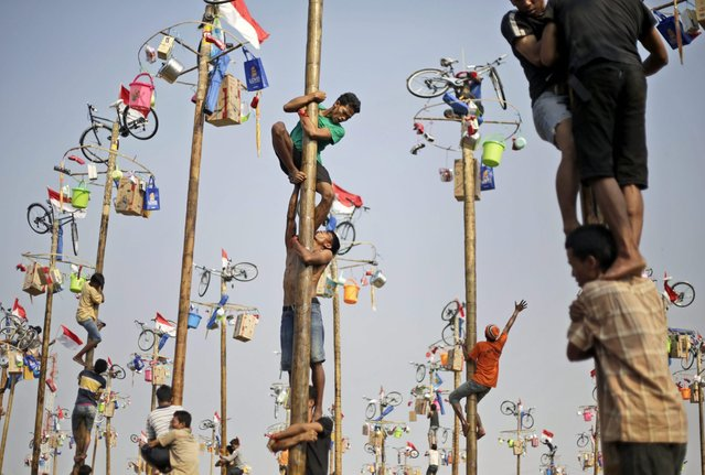 Participants struggle to reach the prizes during a greased-pole climbing competition held as a part of the independence day celebrations in Jakarta, Indonesia, Sunday, August 17, 2014. Indonesia is celebrating its 69th independence from the Dutch colonial rule. (Photo by Dita Alangkara/AP Photo)