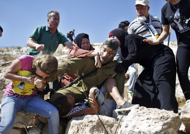 Palestinians scuffle with an Israeli soldier as they try to prevent him from detaining a boy during a protest against Jewish settlements in the West Bank village of Nabi Saleh, near Ramallah August 28, 2015. (Photo by Mohamad Torokman/Reuters)