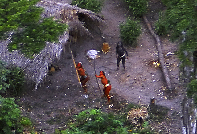 Members of an unknown Amazon Basin tribe and their dwellings are seen during a flight over the Brazilian state of Acre along the border with Peru in this May, 2008 photo distributed by FUNAI, the government agency for the protection of indigenous peoples. Survival International estimates that there are over 100 uncontacted tribes worldwide, and says that uncontacted tribes in the region are under increasing threat from illegal logging over the border in Peru. (Photo by Reuters/Funai-Frente de Proteção Etno-Ambiental Envira)