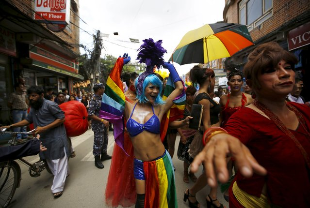 A reveller (C) dances while taking part in a LGBT (lesbian, gay, bisexual and transgender) pride parade to mark Gaijatra Festival, also known as the festival of cows, in Kathmandu, Nepal August 30, 2015. (Photo by Navesh Chitrakar/Reuters)