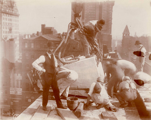Construction workers position a piece of marble on the roof of the central building of the New York Public Library, 1906. (Photo by New York Public Library)
