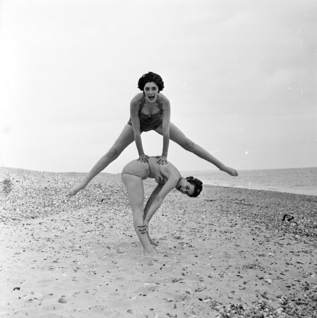 Fashion models Darien Leigh and Valerie Drew play leap-frog on the beach. 2nd July 1956. (Photo by Harry Kerr)