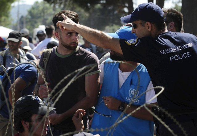 A Greek policeman gestures as migrants wait to enter Macedonia near Gevgelija, at the border with Greece September 1, 2015. (Photo by Ognen Teofilovski/Reuters)