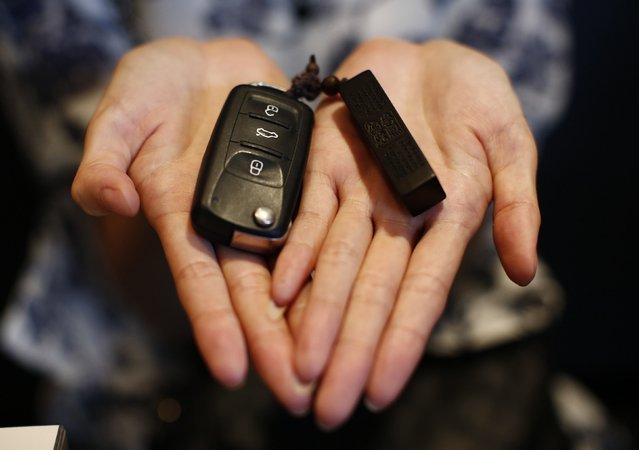 Zhang, whose husband Wang Houbin was onboard Malaysia Airlines Flight MH370 which disappeared on March 8, 2014 shows her husband's car key and key holder during an interview with Reuters in Beijing July 18, 2014. (Photo by Kim Kyung-Hoon/Reuters)