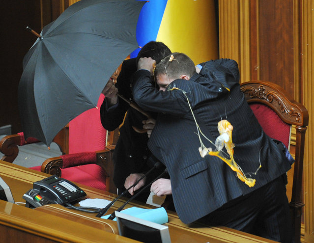 Security personnel protect with umbrellas Speaker of Ukraine's parliament Volodymyr Lytvyn during a fight at a parliament sitting in Kiev on April 27, 2010. Fighting broke out and smoke bombs and eggs were thrown Tuesday as Ukraine's parliament erupted into chaos as it ratified a bitterly controversial deal with Russia extending the lease of a key naval base. The deal signed last week by Russian President Dmitry Medvedev and his Ukrainian counterpart Viktor Yanukovych had been slammed by the pro-Western Ukrainian opposition as a historic surrender of sovereignty. (Photo by Sergei Supinsky/AFP Photo)