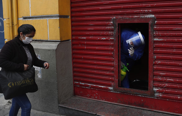 An employee calls for a client to enter a fast food restaurant, during a government lockdown restricting residents to essential shopping in the mornings in an attempt to contain the spread of the new coronavirus, in La Paz, Bolivia, Tuesday, May 5, 2020. (Photo by Juan Karita/AP Photo)