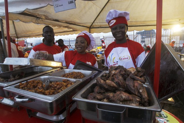 Stall attendants stand behind cooked food during the Festival des Grillades, in the yard of the Culture Palace of Abidjan, September 5, 2015. (Photo by Luc Gnago/Reuters)
